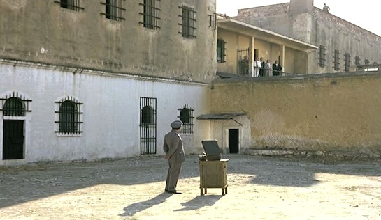 Days of '36 - A record player is brought out to meet one of Sofianos's demands. The officials gather on a balcony next to Sofianos's cell.