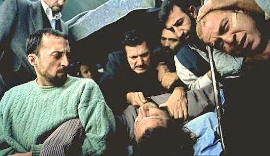 O ?imdi Mahkum - Burhan Öçal as Numan Kolsuz holds a knife to the throat of Levent Kazak (as himself). Gökhan Özo?uz (as himself) is at top right.
