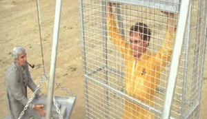 Turkey Shoot #2 - Michael Craig as Camp Master Charles Thatcher, with Steve Railsback as Paul Anders in the punishment cage where the prisoner is required to stop a weight from crushing him